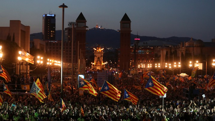 People wave Catalan separatist flags at a rally