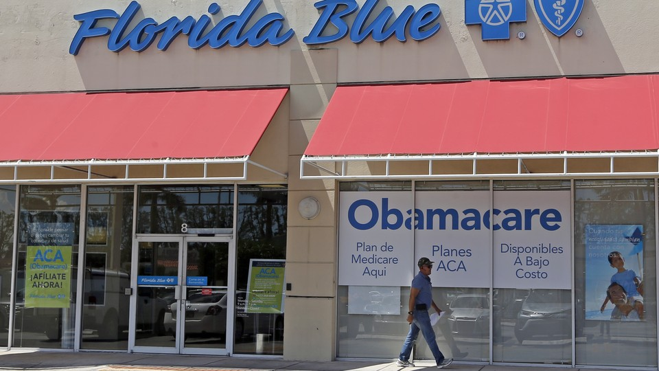 A person walks by a health-care insurance office in Hialeah, Florida.