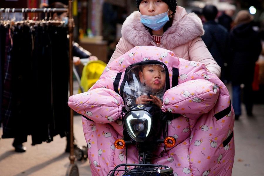 A child, covered in a blanket, peers through a plastic window over the handlebars of a scooter.