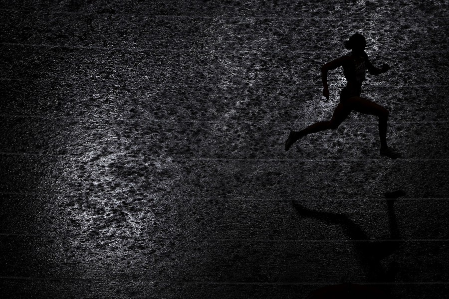 The silhouette of a runner is seen on a rain-soaked track.