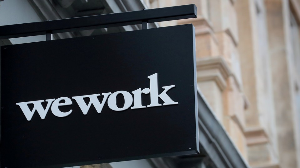 A WeWork sign against some tan buildings