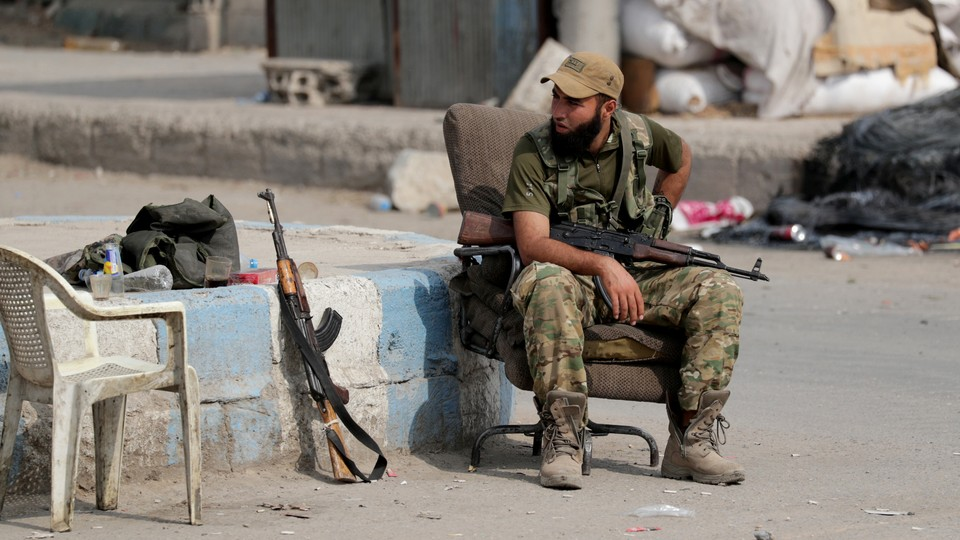 A man dressed in army fatigues sits on a chair holding a gun. Trash is strewn behind him, and an empty white chair and a gun are next to him.