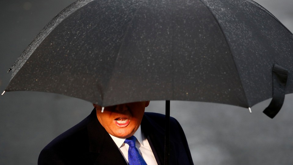 President Donald Trump's face is slightly obscured by a large black umbrella.