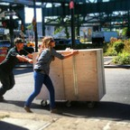 Sam and Leslie Davol push a crate underneath a highway overpass while setting up a pop-up site for the Uni Project