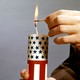 A person's hands holding a red-white-and-blue firecracker while lighting the wick with a match