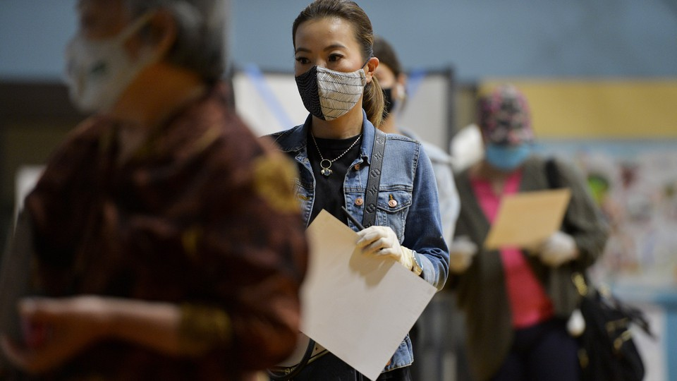 A masked woman waits in line at a polling place.