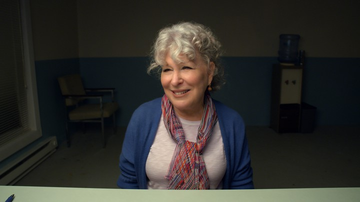 The actor Bette Midler sits at a desk wearing a white shirt and a blue sweater