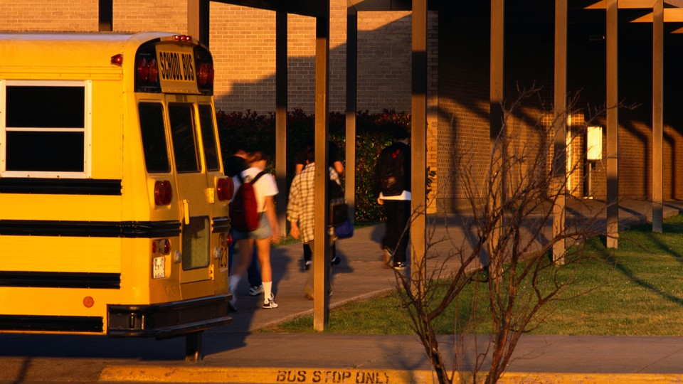 Students get off a school bus.