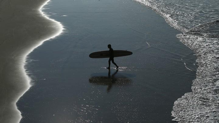 A surfer walks on the beach.