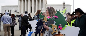 An activist with the League of Women Voters of Maryland carries signs of Maryland's gerrymandered districts outside the U.S. Supreme Court.