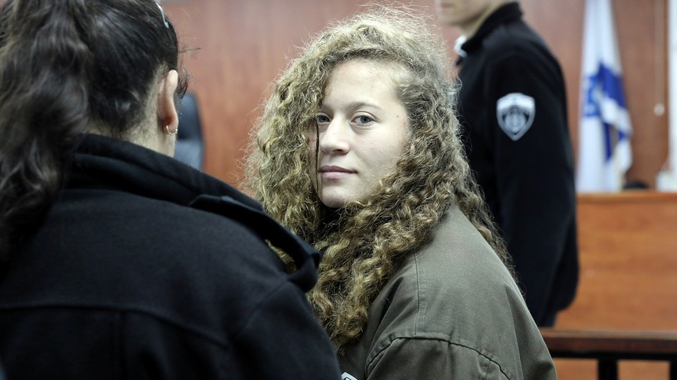 Palestinian teenager Ahed Tamimienters a military courtroom escorted by Israeli authorities at Ofer Prison, near the West Bank city of Ramallah, on January 1, 2018.