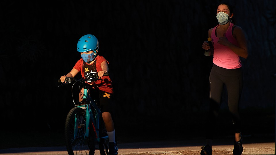 A child wearing a mask rides a bike in front of a masked jogger.