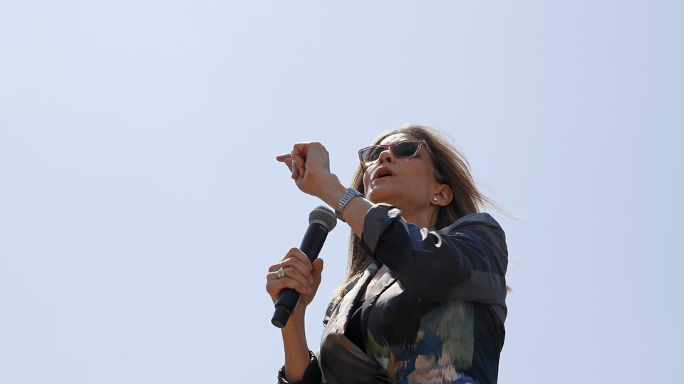 Marianne Williamson speaks into a microphone at the Iowa State Fair. She's wearing sunglasses and a watch, and the blue sky is visible behind her.