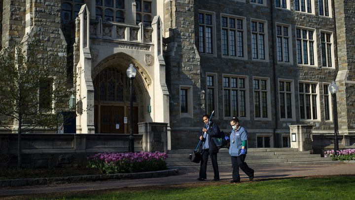 Georgetown University workers walk across campus with cleaning supplies