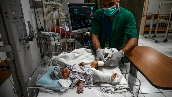 Amina Sharifi, an Afghan newborn, receives treatment for a gunshot wound in her leg.