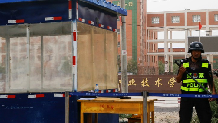 """A guard stands outside what is officially known as a """"vocational skills education center"""" in Hotan in Xinjiang in September 2018."""