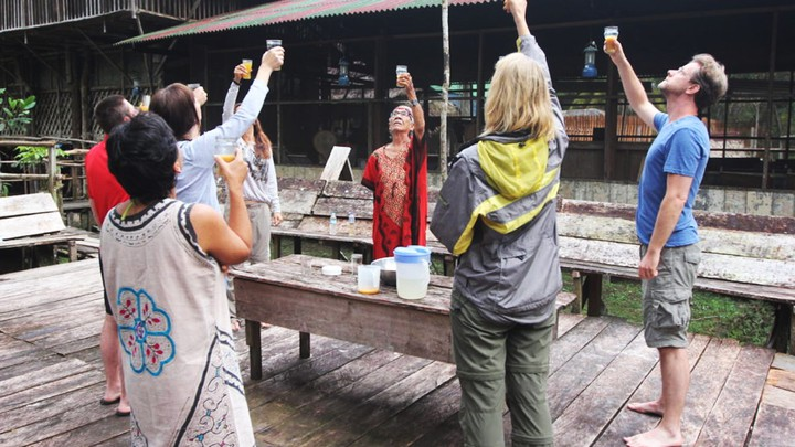 A group of people stands in a circle and raises cups containing a brown liquid.