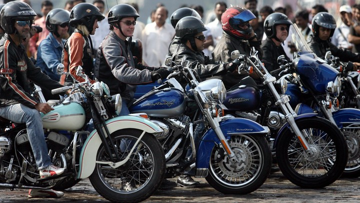 Helmeted riders sit on motorcycles