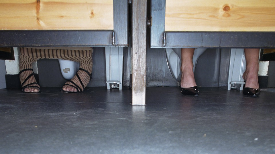 Two women sitting side by side in toilet stalls with their feet visible below the door