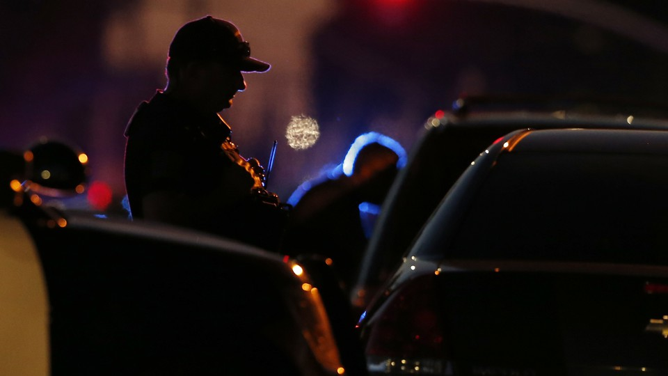 The silhouette of a police officer stopping a car