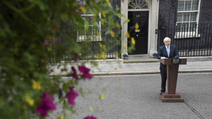 Boris Johnson stands at a lectern on the street outside his 10 Downing Street office.