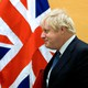 Boris Johnson walks past the flags of the United States and the United Kingdom.