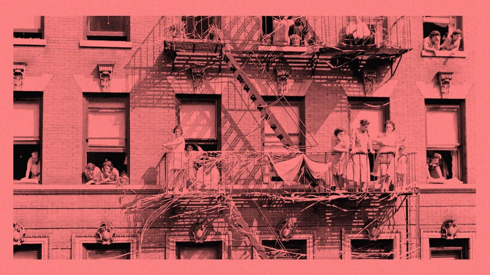 An antique photo of families and children looking out the windows of an apartment building and standing on a fire escape