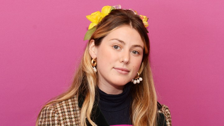 Caroline Calloway stands in front of a pink backdrop looking straight into the camera.