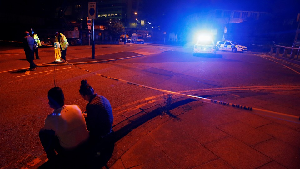 People sit by the side of the road next to a police cordon outside the Manchester Arena.
