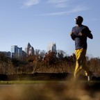 A man jogs along the Atlanta BeltLine park as Midtown high-rises stand in the background.