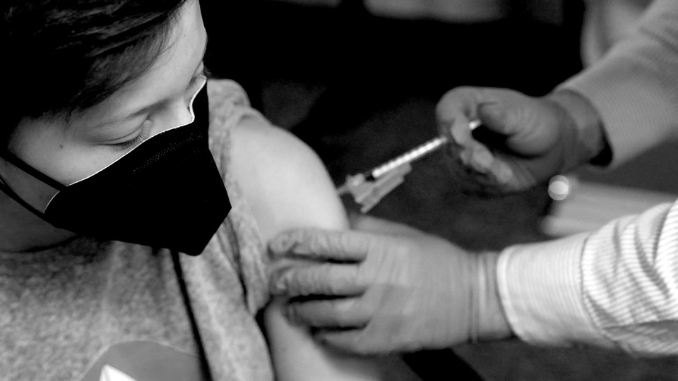 A young person wearing a mask receives a shot in the arm