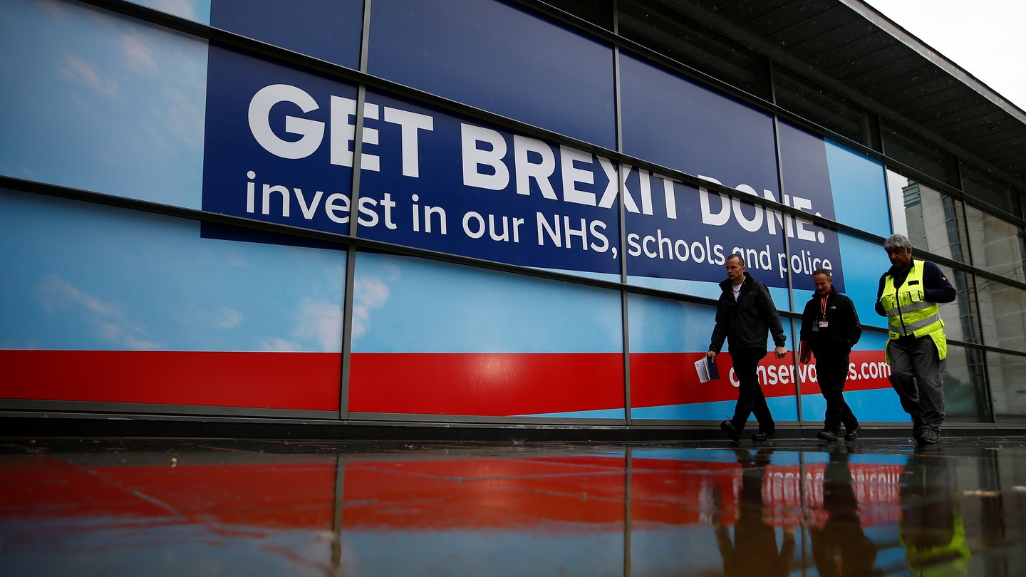 People walk past a Brexit sign outside the venue for the Conservative Party annual conference in Manchester, Britain.