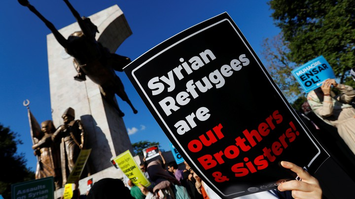 Demonstrators hold placards in support of Syrian refugees during a protest in Istanbul.