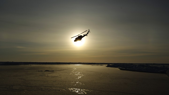 A helicopter flies over Arctic ice toward the Applied Physics Laboratory Ice Station.