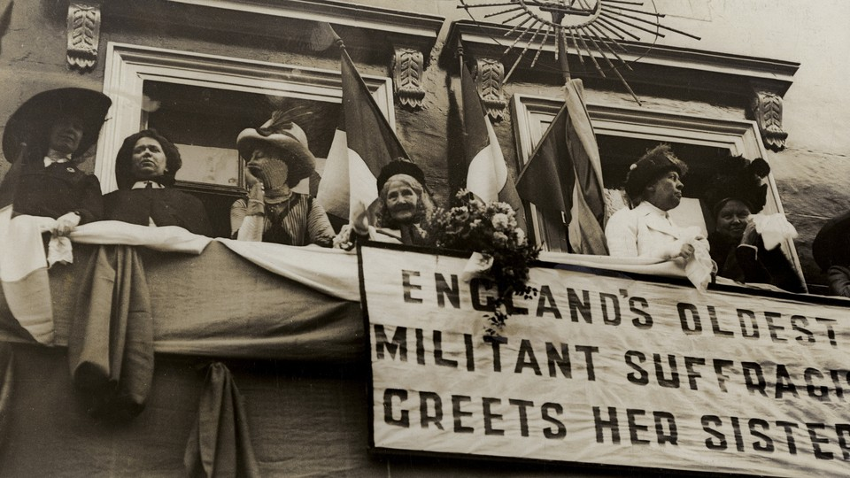 """Elizabeth Wolstenholme Elmy by a banner that reads """"England's Oldest Militant Suffragist Greets Her Sisters"""""""