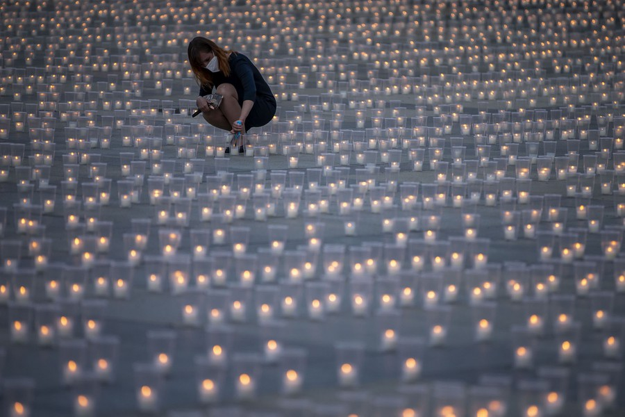 A woman kneels down to light a candle among thousands of other candles arranged in a courtyard.