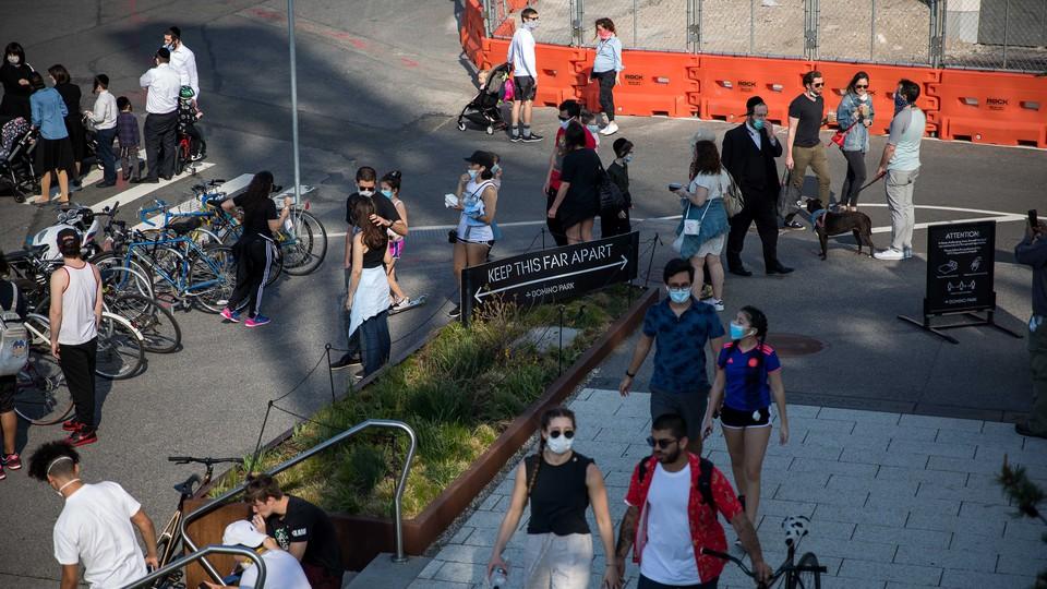 People walk in Domino Park during the coronavirus pandemic in Brooklyn