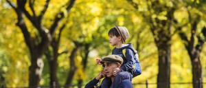 A man carrying a young boy on his shoulders amid the fall foliage of New York's Central Park.