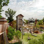 A large adventure playground with towers and slides.