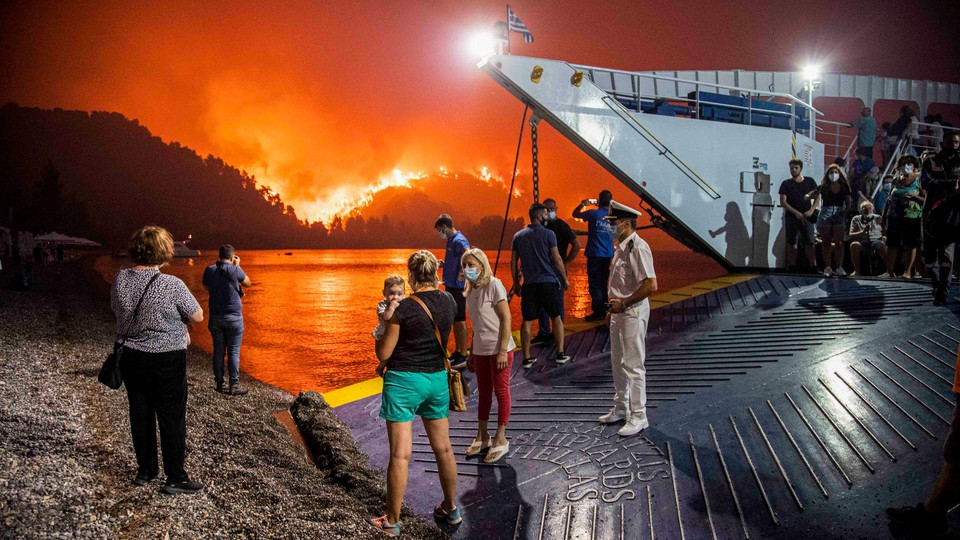 People board a ferry prior to an evacuation as a wildfire approaches the seaside village of Limni, on the island of Evia, Greece, on August 6, 2021.