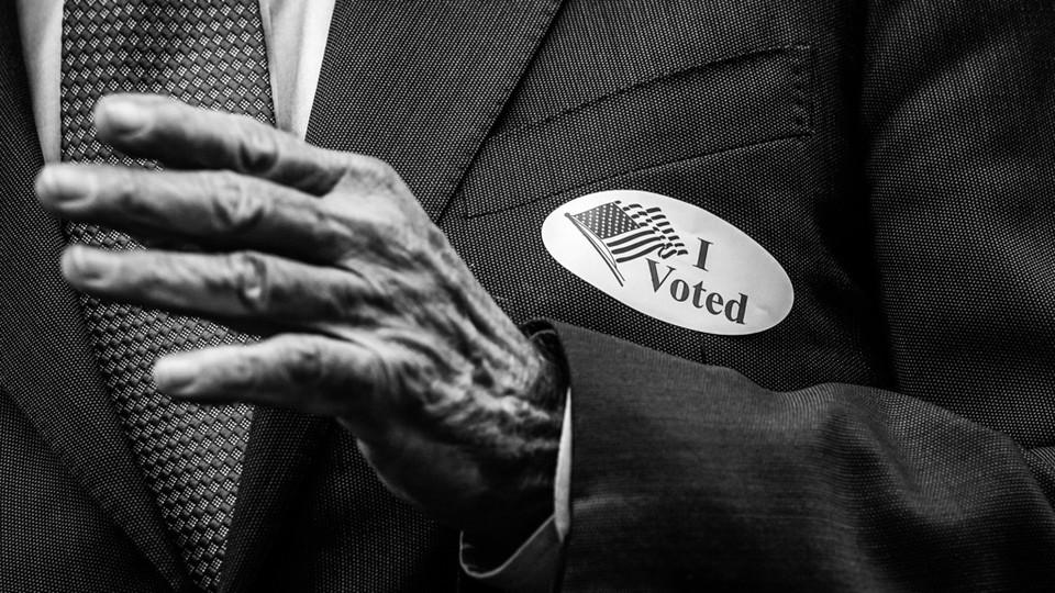 "An elderly person wearing an ""I voted"" sticker"