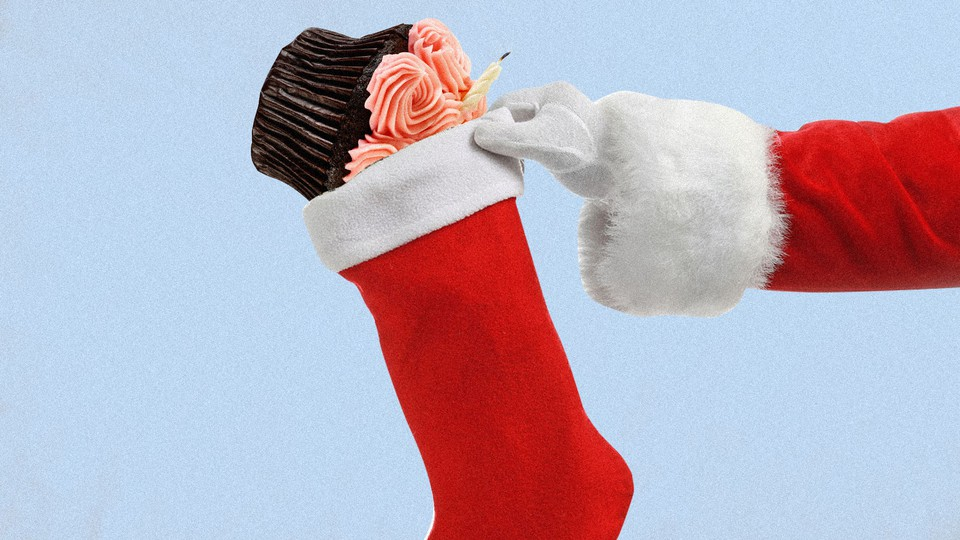 An illustration of a birthday cupcake being placed into a Christmas stocking.