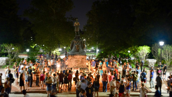 Charlottesville community members are seen leaving candles at the base of a statue of Thomas Jefferson.