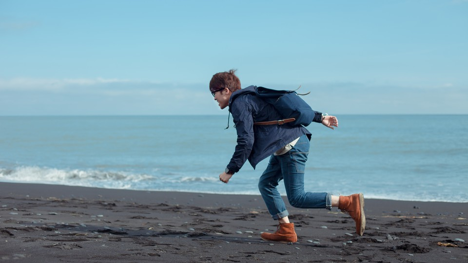 A man running in jeans on the beach