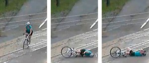 A bicyclist tries to cross railroad tracks and tumbles to the ground.