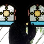 A man prays in front of the stained glass windows of a mosque