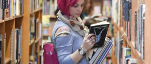 A woman is pictured reading in a bookstore.