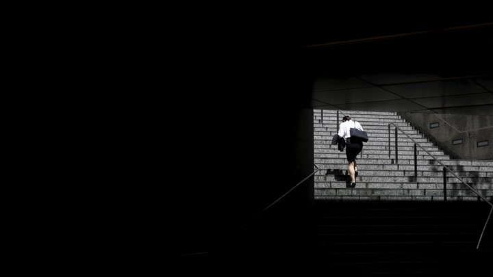 A woman climbs a set of stairs.