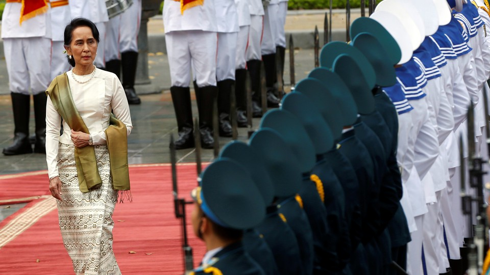Aung San Suu Kyi walks past the honor guard at the presidential palace in Hanoi, Vietnam.