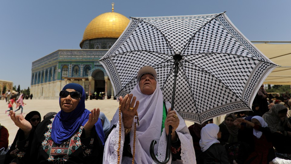 Women with an umbrella praying with their hands outstretched